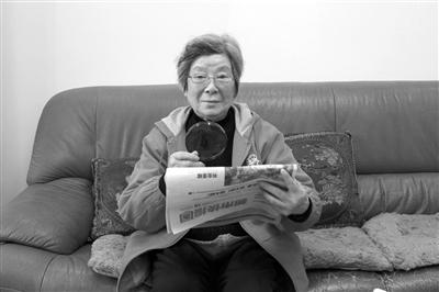 李奶奶在家拿着放大镜看报